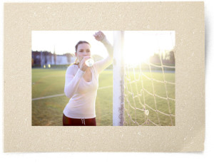Young woman leaning on soccer goal