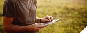 Man using tablet with grass in background