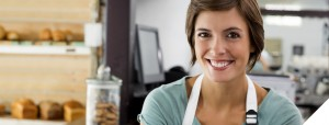 Coffee shop employee with white apron smiling