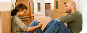 Young couple resting at new home with unpacked boxes all around