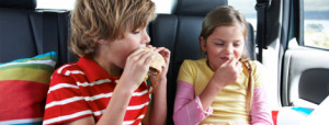 pre-teen bother and sister eating a meal in their car