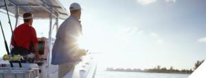 two men fishing in salt water boat wtih sun shining